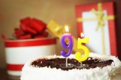 Noventa cinco anos de aniversário Bolo com velas e os presentes ardentes Foto de Stock