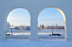 Novgorod Kremlin in Veliky Novgorod, Russia - winter sunset framed view. Towers of Novgorod Kremlin fortress framed by the white stoned arches of Yaroslav Stock Images