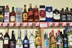 Novi Sad, Serbia, 06.02.2018 alcoholic beverages on the shelf. With prices, yellow wall background royalty free stock images