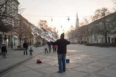 NOVI SAD, SERBIA - 13 DICEMBRE 2015: Esecutore della via che fa le bolle di sapone per divertire la gente che passa dalla st prin Fotografia Stock