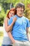 Novia adolescente que abraza a su novio en parque Fotos de archivo