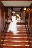 Novia afroamericana bonita que sostiene las flores en las escaleras interiores Fotos de archivo