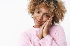 Novia afroamericana hermosa blanda y femenina con la cabeza que se inclina rizada del pelo rubio en las palmas dulces y lindas imagenes de archivo