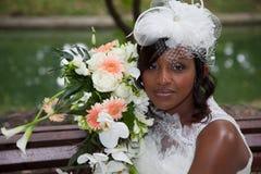 Novia afroamericana hermosa que presenta en su día de boda con el ramo Fotografía de archivo