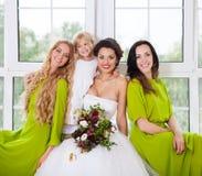 Novia alegre con los amigos femeninos y el pequeño florista Fotos de archivo