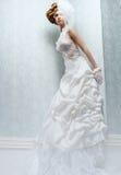 Novia alta con la alineada de boda blanca Imagenes de archivo