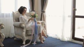 Novia apacible que se sienta en la silla con el ramo de la boda en las manos almacen de video