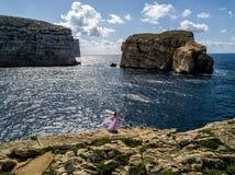 Novia asiática en un vestido de boda que presenta en la costa rugosa de Gozo, Malta imagenes de archivo
