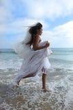 Novia asiática que se ejecuta a lo largo de la playa Fotografía de archivo