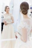 Novia blanda linda hermosa de la chica joven en vestido de boda en espejos con el pelo de la tarde y el maquillaje ligero apacibl fotos de archivo