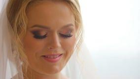 Novia bonita que mira fuera de ventana y que sonríe en su día de boda metrajes