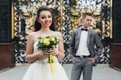 Novia con el ramo y novio en el fondo Fotografía de archivo