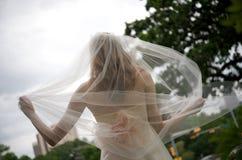 Novia con el velo que fluye detrás de ella Foto de archivo libre de regalías