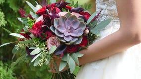 Novia con las flores a disposición al aire libre La novia está nerviosa antes de la boda La novia está llevando a cabo la boda br metrajes
