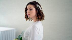 Novia con un ramo de rosas en sus manos que miran la cámara La cámara vuela alrededor de la novia metrajes
