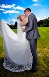 Novia con velo largo que besa al novio en traje Imagen de archivo libre de regalías