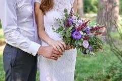 Novia de abarcamiento del novio con el ramo hermoso de la boda Fotografía de archivo libre de regalías