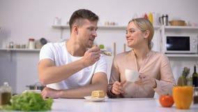 Novia de alimentación del hombre hermoso con la torta, fecha en la cocina, atmósfera romántica almacen de video