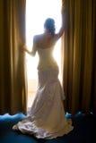 Novia de detrás la mirada a través de las cortinas Foto de archivo