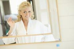 Novia de Gorgerous que se coloca delante del espejo y que fija su pelo imagenes de archivo