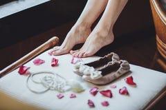 Novia de la mañana Los pies de las novias se cierran para arriba, casandose los zapatos, los pétalos color de rosa Fotos de archivo