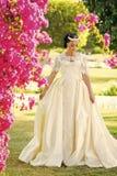 Novia de la muchacha en el vestido de boda que presenta en el prado Fotos de archivo libres de regalías