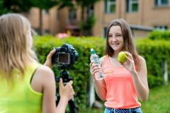 Novia de la muchacha en las manos que sostienen una botella de agua y de una manzana verde En verano él escribe el vídeo a la cám foto de archivo libre de regalías
