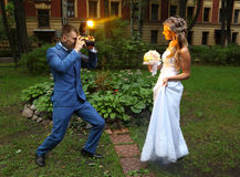 Novia de Taking Picture del fotógrafo de la boda, el destellar de destello de la cámara Foto de archivo