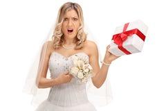 Novia descontentada que lleva a cabo un regalo de boda foto de archivo libre de regalías