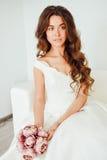 Novia El modelo de moda joven con la piel perfecta y compone, el fondo blanco, pelo rizado, flores Foto de archivo