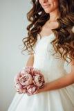 Novia El modelo de moda joven con la piel perfecta y compone, el fondo blanco, pelo rizado, flores Imágenes de archivo libres de regalías