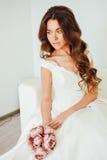Novia El modelo de moda joven con la piel perfecta y compone, el fondo blanco, pelo rizado, flores Fotografía de archivo libre de regalías