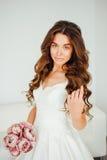 Novia El modelo de moda joven con la piel perfecta y compone, el fondo blanco, pelo rizado, flores Fotografía de archivo