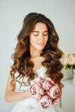 Novia El modelo de moda joven con la piel perfecta y compone, el fondo blanco, pelo rizado, flores Foto de archivo libre de regalías