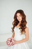 Novia El modelo de moda joven con la piel perfecta y compone, el fondo blanco, pelo rizado, flores Fotos de archivo libres de regalías