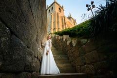 Novia elegante hermosa cerca de la iglesia en las escaleras Fotos de archivo libres de regalías