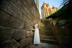 Novia elegante hermosa cerca de la iglesia en las escaleras Imagen de archivo