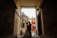 Novia elegante que abraza suavemente al novio en patio viejo en europeo Imágenes de archivo libres de regalías