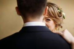 Novia elegante que mira y que abraza suavemente al novio en patio viejo Fotos de archivo