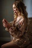 Novia elegante que sostiene en manos una botella de perfume de lujo Fotos de archivo