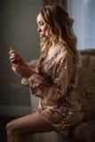 Novia elegante que sostiene en manos una botella de perfume de lujo Fotos de archivo libres de regalías