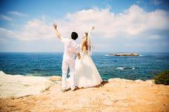 Novia elegante y novio que caminan en la playa, ceremonia de boda, mar Mediterráneo Imagen de archivo
