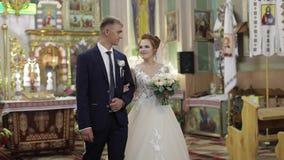 Novia elegante y novio que caminan junto en una iglesia vieja Pares de la boda almacen de metraje de vídeo