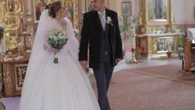 Novia elegante y novio que caminan junto en una iglesia vieja Pares de la boda almacen de video