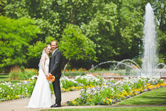 Novia elegante y novio que presentan junto al aire libre en un día de boda Fotos de archivo