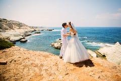 Novia elegante y novio sonrientes que caminan en la playa, besándose, ceremonia de boda, mar Mediterráneo Fotos de archivo
