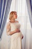 Novia embarazada hermosa que presenta contra ventana Imagenes de archivo