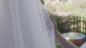 Novia emocionada que toca y que acaricia su vestido que se casa maravilloso blanco en una luz romántica brillante metrajes