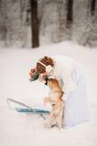 Novia en el invierno que juega con el perro Imagen de archivo