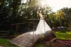 Novia en el puente de madera en el bosque fotos de archivo libres de regalías